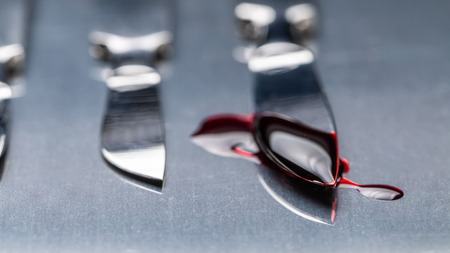 Stainless steel scalpels on stainless steel table with blood