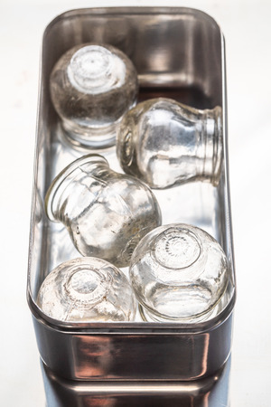 Old medical cupping glass in a stainless steel container