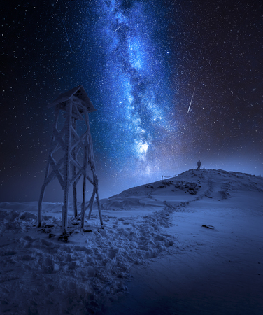 Milky way over a man in winter mountains Stock Photo
