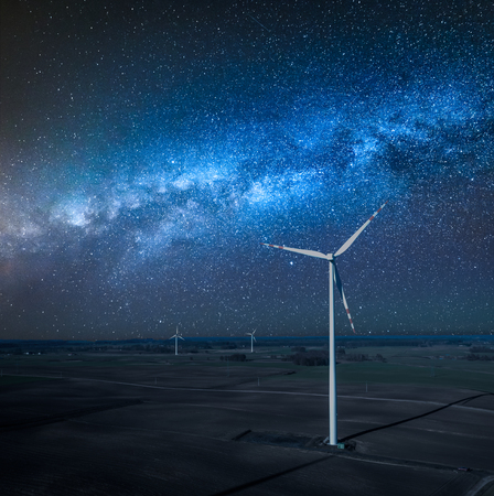 Milky way over wind turbines as alternative energy at night