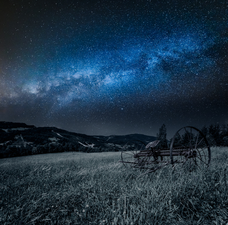 Red rake in a field and milky way