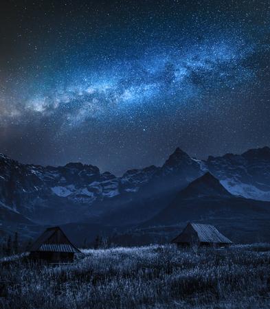 Vía Láctea sobre la montaña Tatra y pequeñas cabañas, Polonia