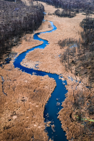 Flying above winding river and brown swamps Stock Photo