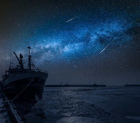 Ship on a frozen sea in winter and milk way