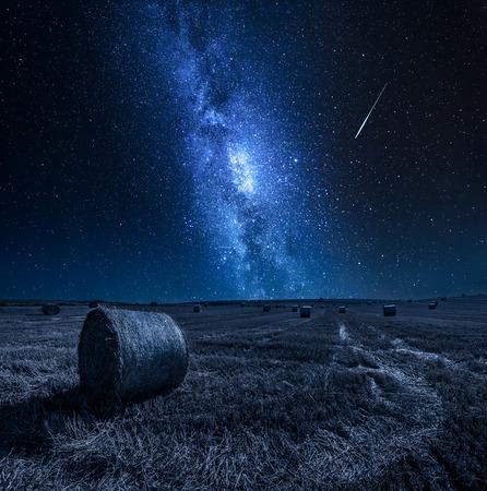 Milchstraße und Feld mit Heu in der Nacht
