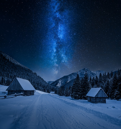 Milky way over small cottages in winter Tatra mountains, Poland