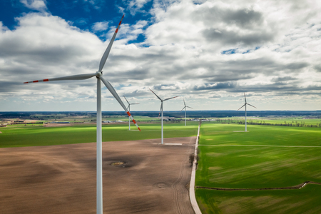Flying above white wind turbines in a field Banco de Imagens