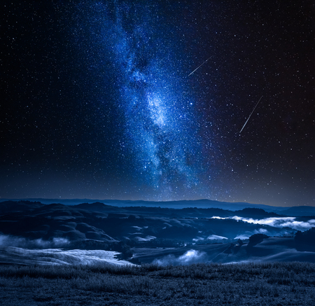 Milky way with falling stars and foggy valley in Italy