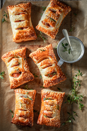 Fresh sausage in puff pastry with tatar sauce and herbs