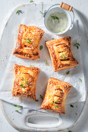 Hot sausage in puff pastry with tatar sauce and herbs