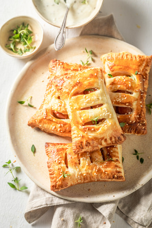 Delicious sausage in puff pastry with thyme and sesame seeds