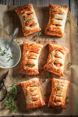 Hot sausage roll with tatar sauce and herbs