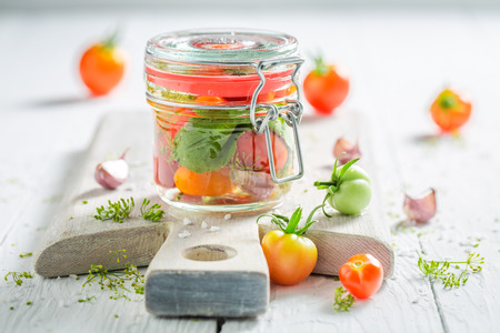 Homemade pickled red tomatoes in small jar
