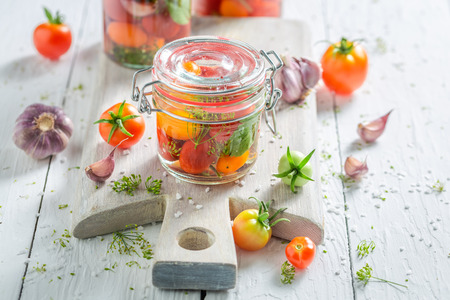Preparation for canned red tomatoes on wooden table