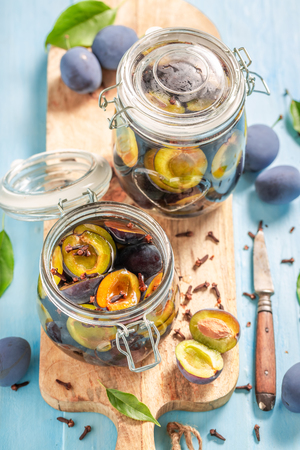 Top view of pickled plums in jar on blue table