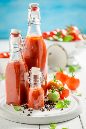 Homemade and tasty ketchup prepared from tomatoes on white table