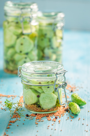 Homemade canned cucumber in the jar on blue table