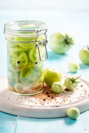 Homemade pickled green tomatoes in the jar on wooden table