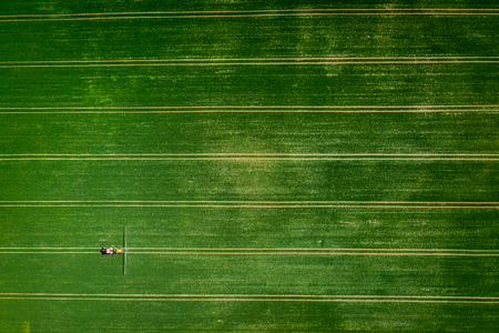 Flying above tractor spraying the pesticides on the field, Poland Stock fotó