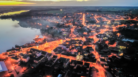 Flying above downtown by lake with smog at sunset, Poland