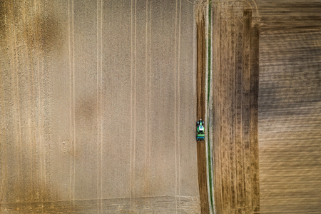 Green tractor plowing a spring field, Poland, aerial view