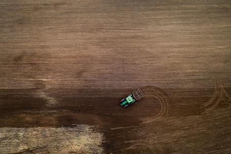 Green tractor working on spring field, aerial view, Poland