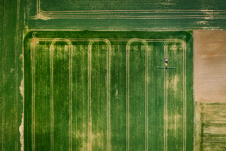 Small tractor spraying the pesticides on the field, aerial view