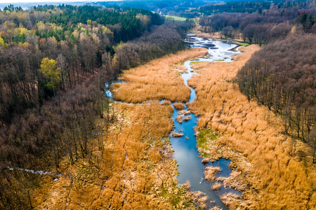 Aerial view of small winding river in brown swamps Stockfoto