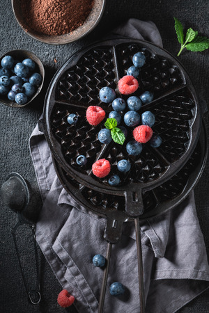 Tasty waffles with dark chocolate and berry fruits as concept 写真素材