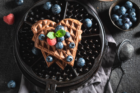Delicious waffles made of cocoa with berry fruits