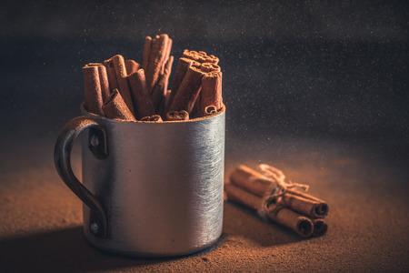 Cinnamon powder and bark in an old rustic mug Stockfoto