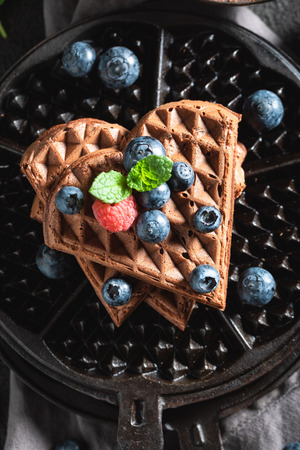 Yummy waffles with dark chocolate and berry fruits