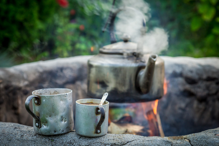 Fresh and hot coffee with kettle on campfire 写真素材