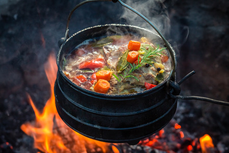Tasty and spicy hunters stew on bonfire