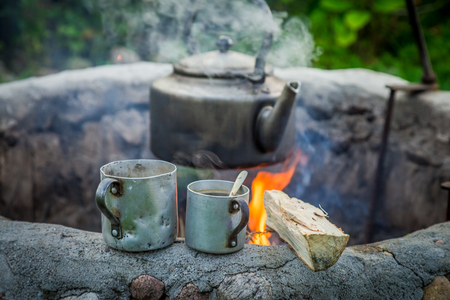 Hot aromatic coffee with kettle on bonfire in summer