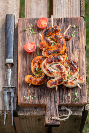 Top view of grilled and twisted sausage in summer