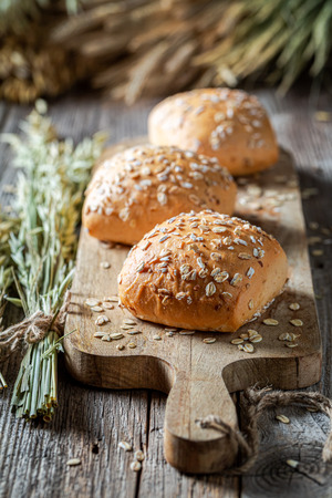 Healthy and fresh rolls with oat flakes on wooden table Stock Photo