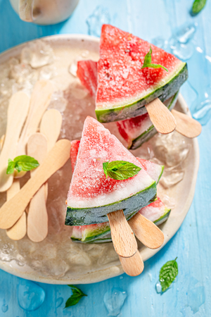 Watermelon ice cream on a stick with mint Imagens