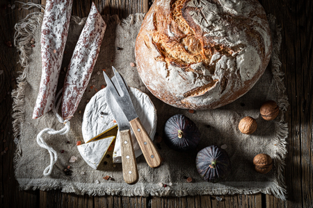 Fresh bread with camembert cheese, nuts and sausage Imagens