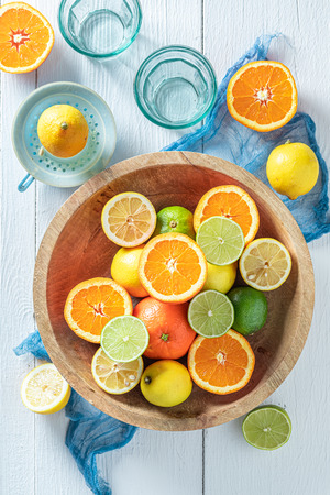 Top view of oranges, limes and lemons on wooden table