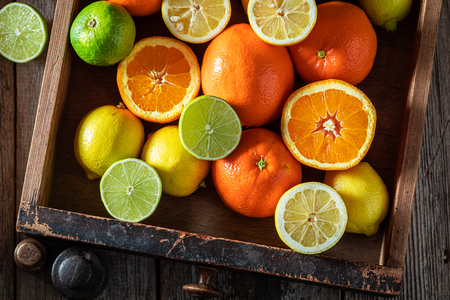 Tasty and sweet oranges, limes and lemons on rustic table
