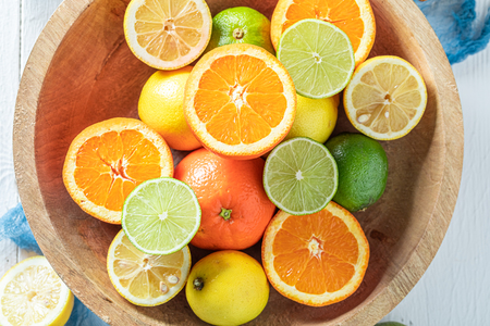 Top vie of oranges, limes and lemons on white table