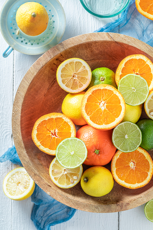 Fresh and healthy oranges, limes and lemons on wooden table