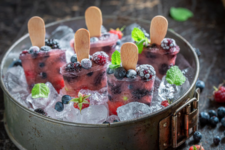 Homemade and cold berry fruits ice cream on a stick