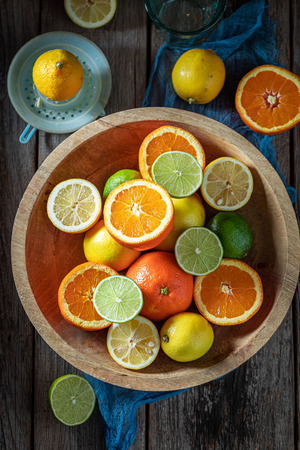 Tasty mix of citrus fruits on old wooden table