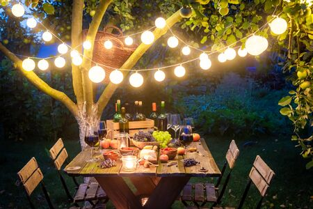 Supper with tasty appetizers and wine in summer evening