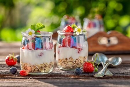 Closeup of granola in jar with yoghurt and berries