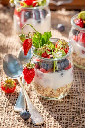 Homemade oat flakes in jar with berries and yogurt