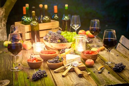 Closeup of table with snacks and wine in illuminated garden