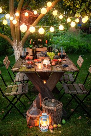 Preparation for supper with wine in illuminated summer garden Фото со стока